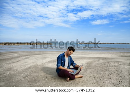 Young man sitting on beach with laptop - stock photo