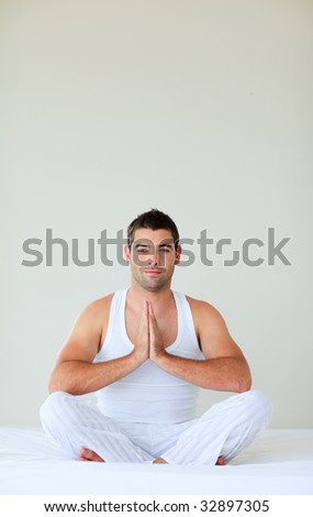 Young man sitting on bed meditating with copy-space - stock photo