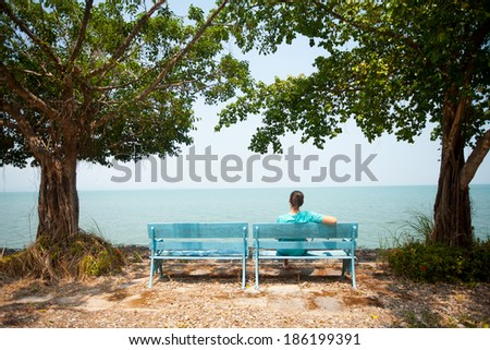 Young man sitting on bench facing the sea in Thailand - stock photo