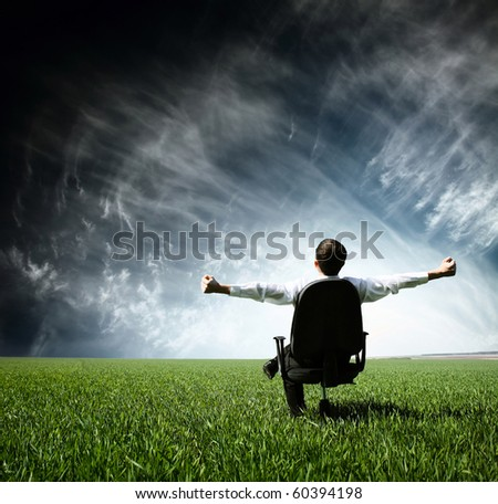 Young man sitting on chair in green meadow - stock photo