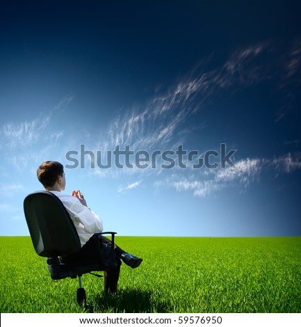 Young man sitting on chair in green meadow and looking to a blue sky with clouds