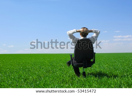 Young man sitting on chair on meadow with green grass - stock photo