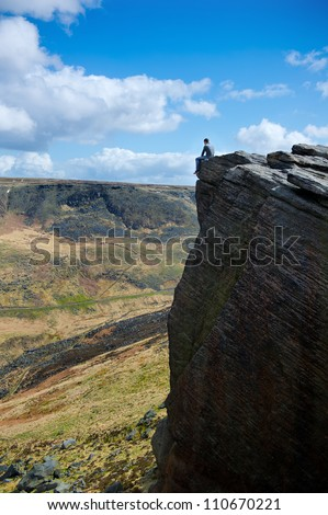 Young man sitting on cliff's edge and looking to a sky with clouds - stock photo