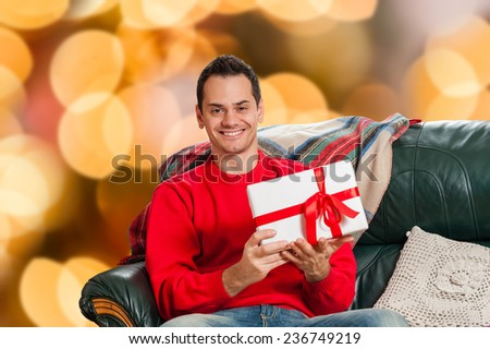 Young man sitting on couch, alone,holding a gift box over isolated christmas colorful lights background - stock photo