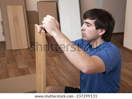Young man sitting on floor assembling flatpack closet - stock photo