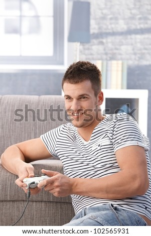 Young man sitting on floor at home, playing video gam, smiling. - stock photo