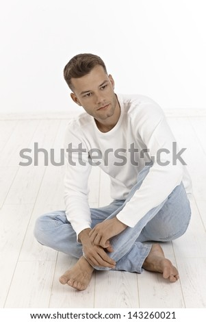 Young man sitting on floor in tailor seat, thinking, looking away.