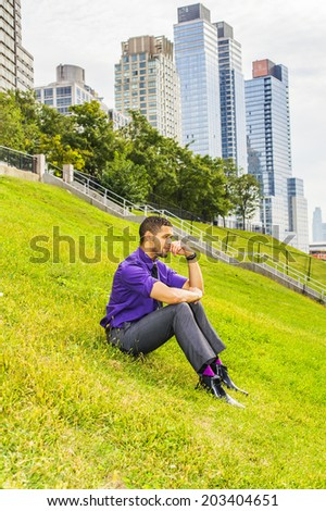 Young Man Sitting on Grasses. Dressing in a purple shirt, gray pants, a black tie, leather shoes, a young handsome businessman is sitting outside a business district, relaxing, thinking. - stock photo