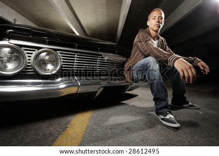 Young man sitting on his custom car - stock photo