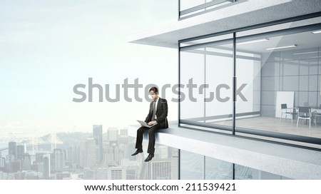 young man sitting on skyscrapper with laptop - stock photo