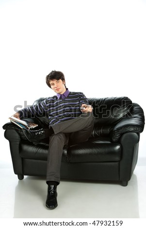 young man sitting on sofa and reading magazine, isolated in white