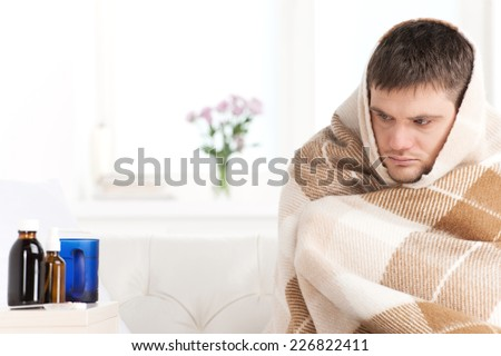 young man sitting on sofa covered with blanket. sick man looking tired and ill looking at bottles - stock photo