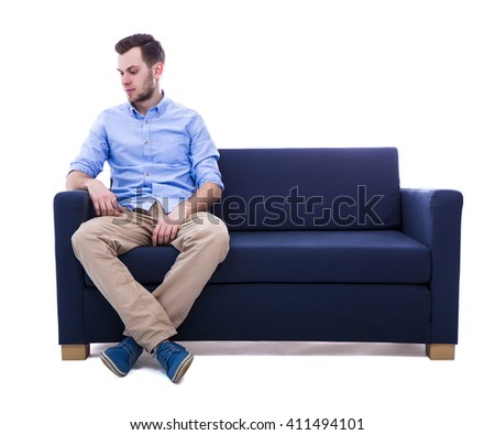 young man sitting on sofa isolated on white background - stock photo