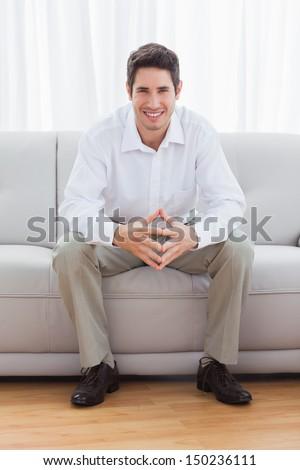 Young man sitting on sofa smiling at camera - stock photo
