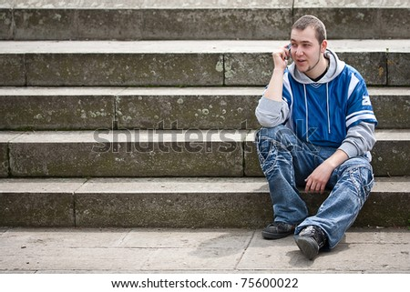 Young man sitting on stairs and talking on the phone - stock photo