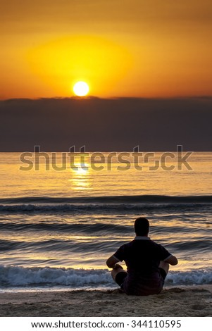 Young man sitting on the beach contemplating sunrise or sunset behind wall of clouds - stock photo