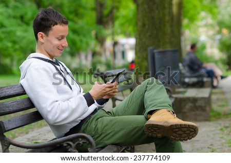 Young man sitting on the bench in the park and using tablet device on beautiful spring day. - stock photo