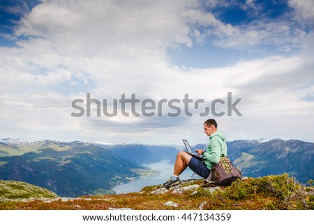 Young man sitting on the cliff using laptop - stock photo