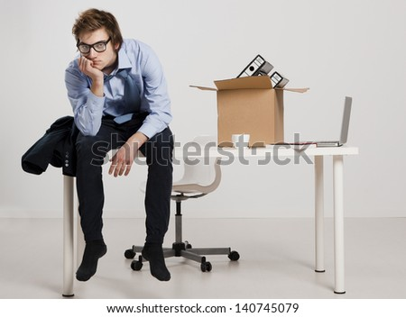 Young man sitting on the desk after being fired