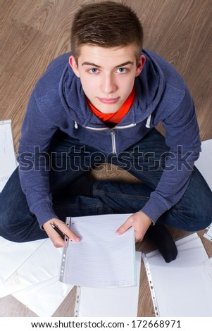 young man sitting on the floor and learning - top view - stock photo
