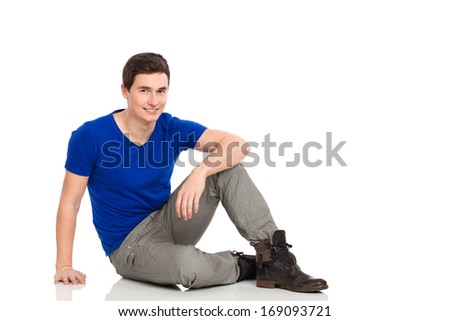 Young man sitting on the floor. Full length studio shot isolated on white. - stock photo