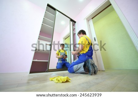 Young man sitting on the floor secures door sliding wardrobe in room with pink walls - stock photo