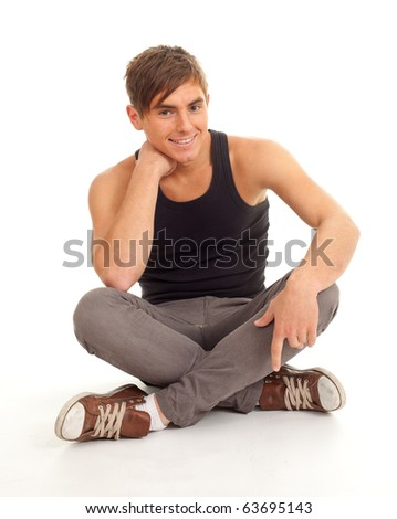 young man sitting on the floor with crossed legs - stock photo