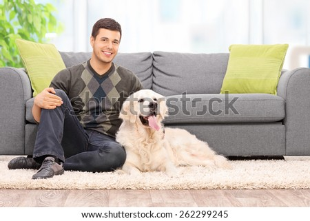 Young man sitting on the floor with his dog at home  - stock photo