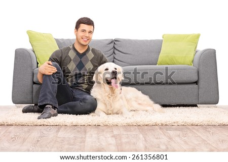 Young man sitting on the floor with his dog isolated on white background - stock photo