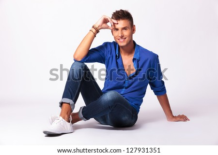 young man sitting on the floor with legs crossed and holding his forehead is smiling to the camera on a gray background - stock photo