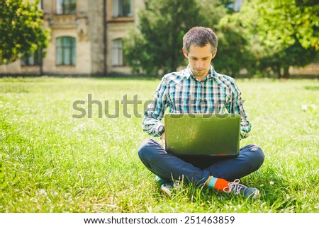 Young man sitting on the grass and working on laptop - stock photo