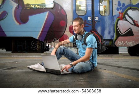 Young man sitting on the platform of a train station and using a laptop - stock photo