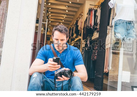 young man sitting on the road in front of a store - stock photo