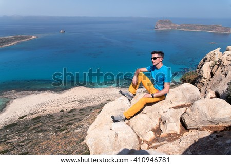young man sitting on the rock in front of the sea - stock photo