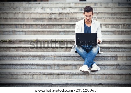 Young man sitting on the stairs using laptop - stock photo