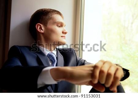 Young man sitting on windowsill - waiting bride - stock photo