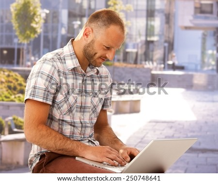 Young man sitting outdoors, using laptop at summertime. - stock photo