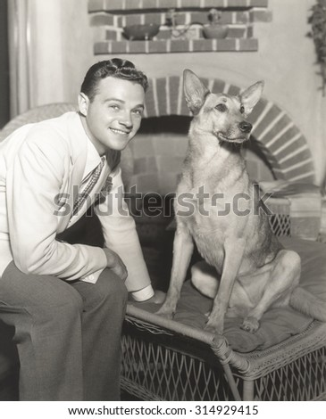 Young man sitting with dog at home - stock photo