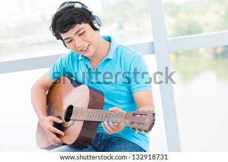 Young man sitting with guitar and in headphones - stock photo