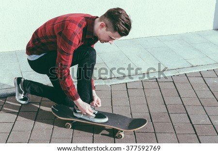 Young man skater tying a shoelaces on the street - stock photo