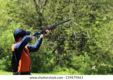Young man skeet shooting - stock photo