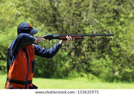 Young man skeet shooting - stock photo