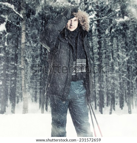 Young man skier wearing black fur hood winter jacket and holding sticks in winter forest  - stock photo