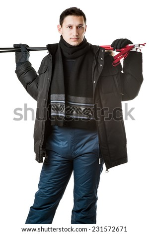 Young man skier wearing black fur hood winter jacket and pants holding sticks isolated on white background