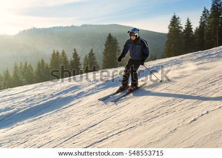 Young man skiing on the slope of winter resort