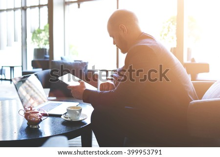 Young man skilled CEO is checking time while is waiting with touch pad and net-book international partners. Male restaurant owner with portable digital tablet in hand is looking on his wrist watch - stock photo