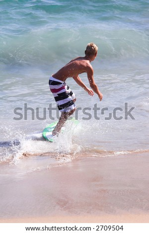Young man skimboarding in the surf on Balboa Beach, Balboa California