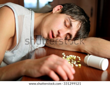 Young Man sleep near the Pills on the Table at the Home