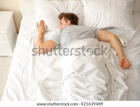 Young man sleeping alone in white big bed - stock photo