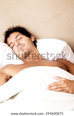 Young man sleeping in bed - stock photo